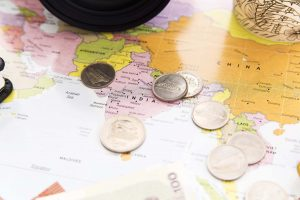 Different money and coins sitting on a map.
